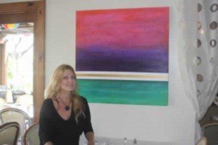 La Jolla artist Kim McBride with one of her paintings at Barbarella Restaurant in La Jolla Shores. Ashley Mackin
