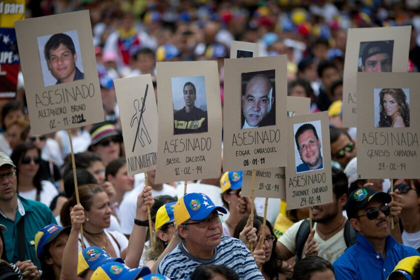 Demonstrators hold up posters with images of Venezuelans who were killed in the past two weeks during the recent unrest, at a rally with human rights activists in Caracas, Venezuela, Friday, Feb. 28, 2014. The start of a weeklong string of holidays leading up to the March 5 anniversary of former Pr