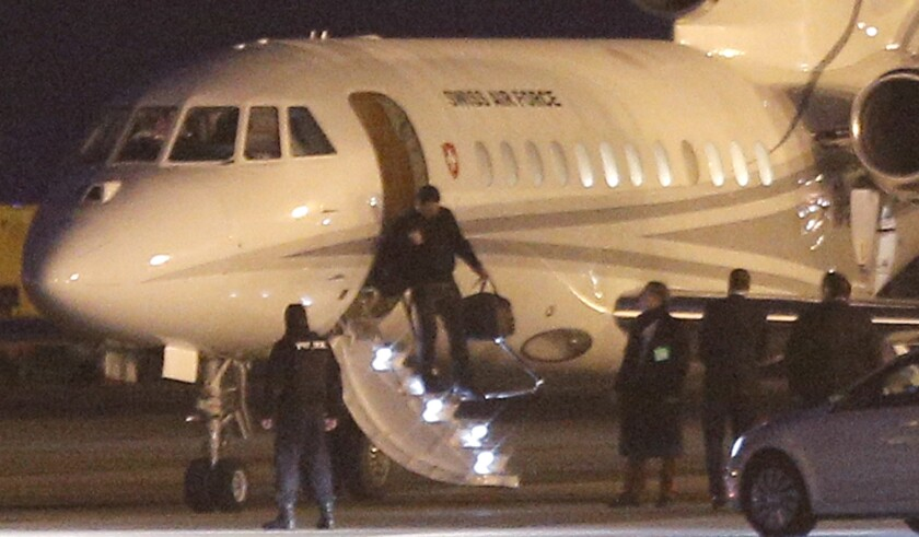 An unidentified man leaves a Swiss air force Dassault Falcon at the airport in Geneva on Sunday, as a U.S. government plane waited nearby for the men who were released from imprisonment in Iran the day before.