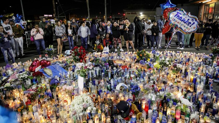 Community members remember slain rapper Nipsey Hussle at a makeshift memorial outside his South L.A. clothing store on Tuesday.