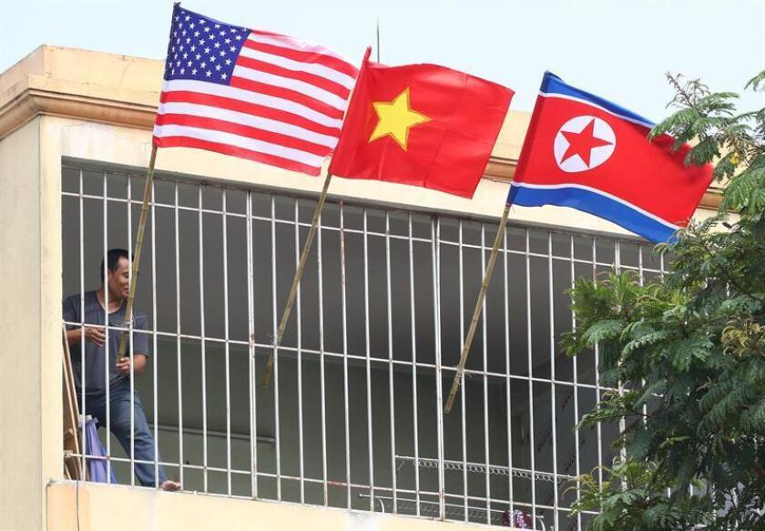 A resident places the American, Windward and North Korean flags on the terrace of his house located near the JW Marriot Hotel in Hanoi, Vietnam. On Feb. 21, 2019. EPA-EFE / Yonhap / PROHIBITED USE IN SOUTH KOREA