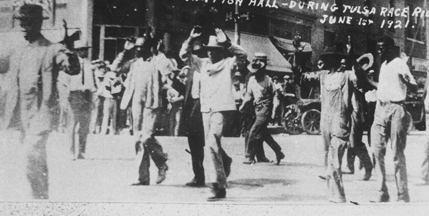 Black detainees walk with their hands up after the 1921 race massacre in Tulsa, Okla.