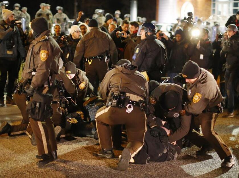 Varios policías detienen a unos manifestantes a las afueras del Departamento de Policía de Ferguson. EFE/Archivo
