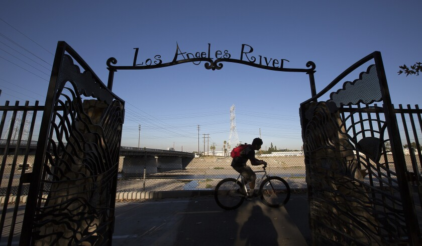 A man rides a bike along the Los Angeles River in Maywood.