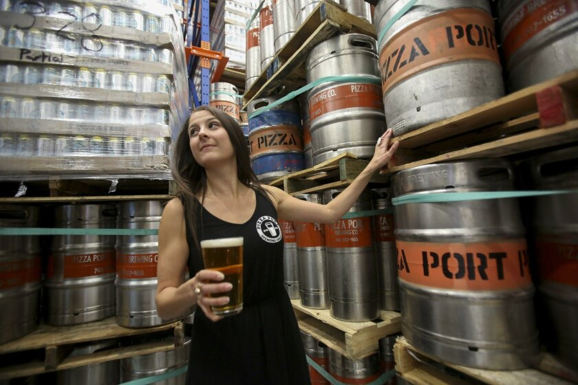 Sales and Brand Ambassador for Pizza Port Jill Davidson, who is also Vice President of the San Diego Brewers Guild, checks out the stock of beer in cold storage of the brewing facility at Pizza Port in Bressi Ranch. Bill Wechter