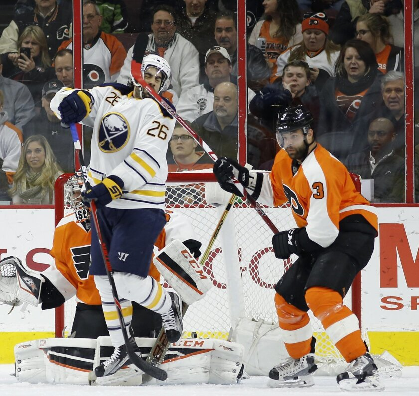 Buffalo Sabres' Matt Moulson (26) takes a stick to the head from Philadelphia Flyers' Radko Gudas (3) during the second period of an NHL hockey game, Thursday, Feb. 11, 2016, in Philadelphia. (AP Photo/Matt Slocum)