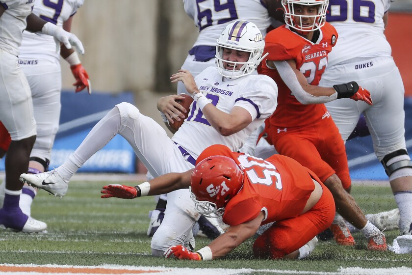 James Madison quarterback Cole Johnson (12) is sacked by Sam Houston State linebacker Ysidro Mascorro (50) during the fourth quarter of a semifinal game in the NCAA college football FCS playoffs, Saturday, May 8, 2021, in Huntsville, Texas. Sam Houston came from behind to edge James Madison 38-35, for a berth in the FCS national championship game. (Brett Coomer/Houston Chronicle via AP)