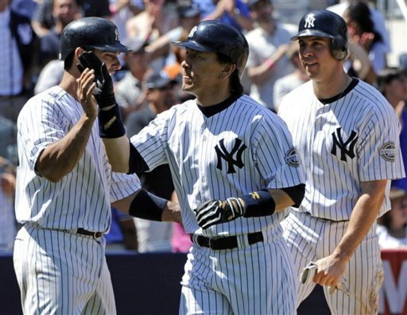New York Yankees' Hideki Matsui, center, celebrates with teammates Jorge Posada, left, and Mark Teixeira, right, after hitting a three-run home run to score both players against the Toronto Blue Jays during the fourth inning of a baseball game Sunday, July 5, 2009, at Yankee Stadium in New York. (AP Photo/Bill Kostroun)