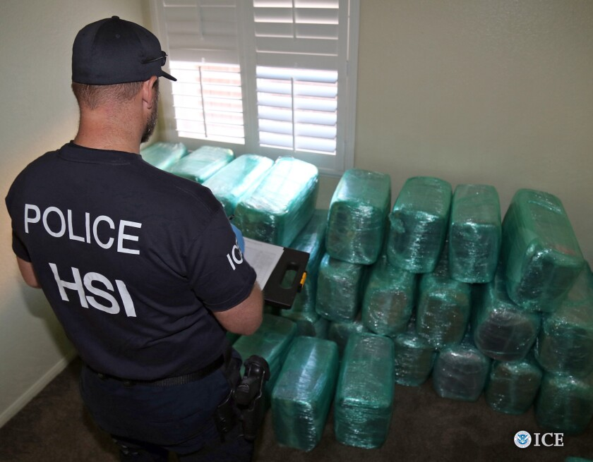 An investigator examines bags of marijuana stored in a room of a newly built home in Calexico, the terminus of a cross-border tunnel from a restaurant in Mexico.