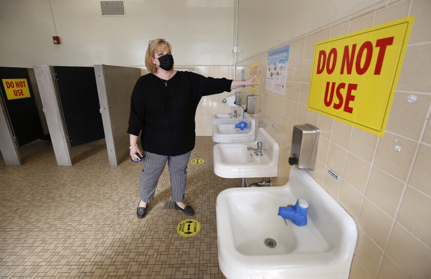 An elementary school principal points to taped-off sinks and closed stalls in a school bathroom.