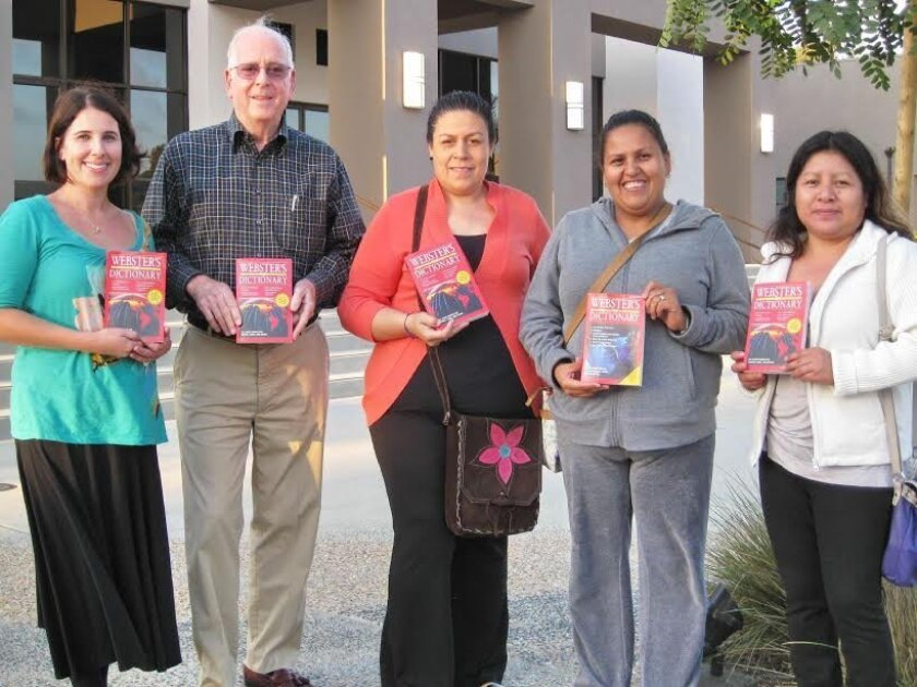 L-R: Nicole Mione-Green, executive director of Casa de Amistad, Rotarian Charles Foster, and three students in Casa de Amistad's adult education class (holding copies of donated dictionaries).