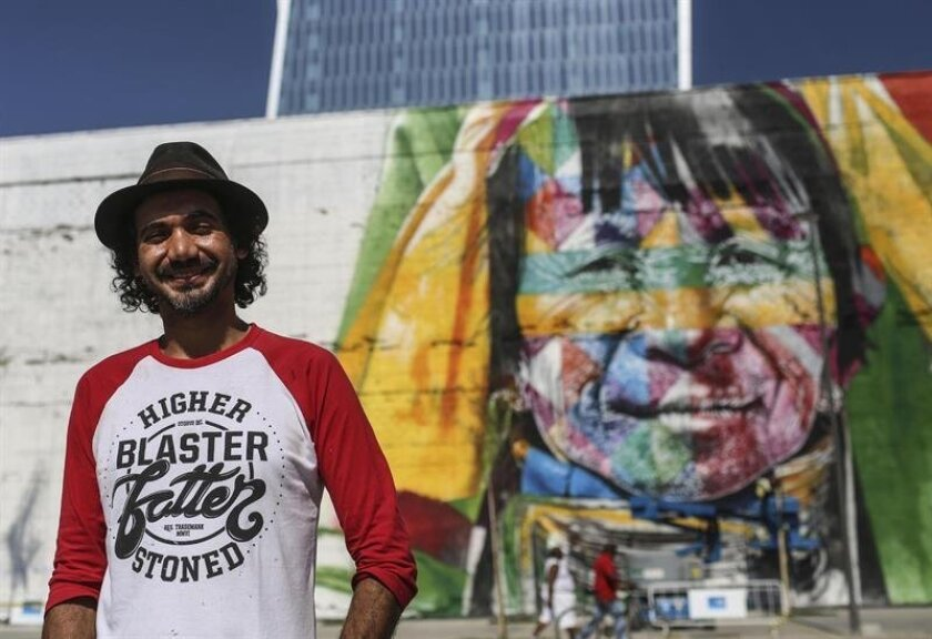 A man sweeps along a mural, showing a Karen woman from Thailand, one of the five giant faces of indigenous people from five nations on five continents, on International Day of the World's Indigenous Peoples, called 'Etnias' (Ethnicities) by Brazilian graffiti artist Eduardo Kobra, on the Olympic Bo