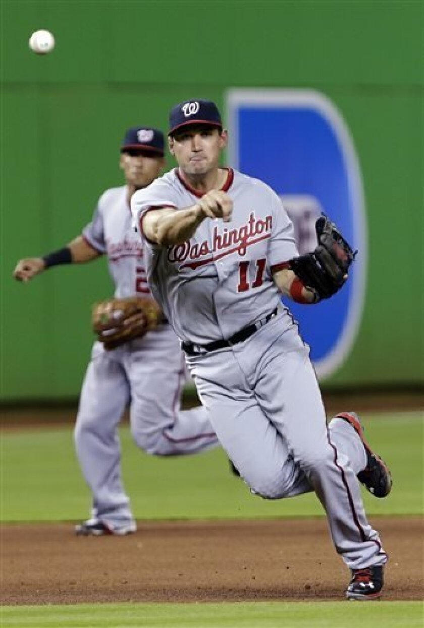 Washington Nationals third baseman Ryan Zimmerman (11) commits a throwing error as he tries to put out Miami Marlins' Placido Polanco at first base during the fourth inning of a baseball game, Tuesday, April 16, 2013, in Miami. Behind Zimmerman is shortstop Ian Desmond. The Marlins won 8-2. (AP Pho