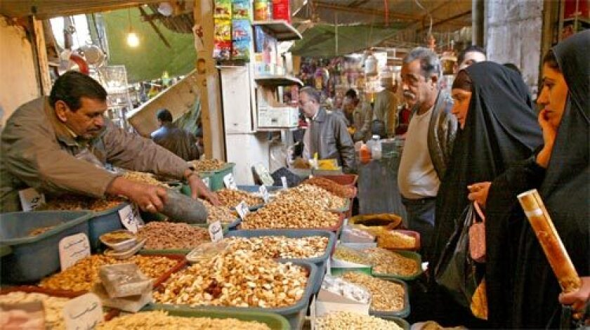 IN BAGHDAD: Iraqis purchase nuts at a market before Eid al-Adha festivities that commemorate the prophet Abraham's willingness to sacrifice his son for God. Sunnis in many Iraqi cities say the security gains have allowed them to fully celebrate the holiday.