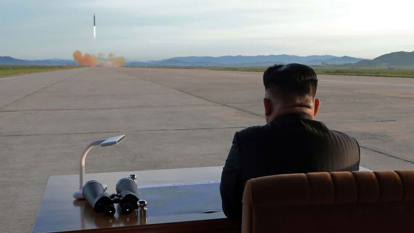 North Korean leader Kim Jong-un watches a missile launch.