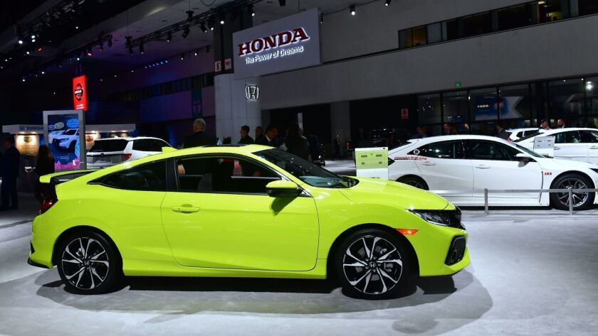 New Honda Civics, including a yellow Civic Si 2-door, on display at AutoMobility L.A., the trade show ahead of the L.A. Auto Show, on Nov. 28 at the Los Angeles Convention Center.