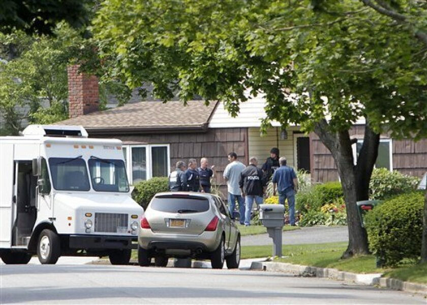 Suffolk County police gather near the door of a house before escorting two people out of the house near a pharmacy where four people were shot to death Sunday during a drug robbery in Medford, N.Y., Wednesday, June 22, 2011. (AP Photo/Seth Wenig)