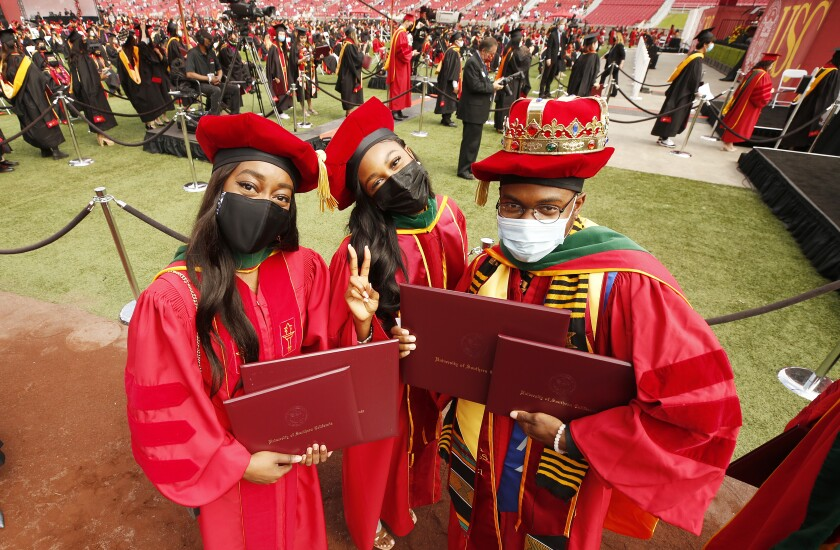 Aleeson Eka, Josephine Nwokedi and Lawrence Rolle celebrate their dual diplomas in medicine and business.