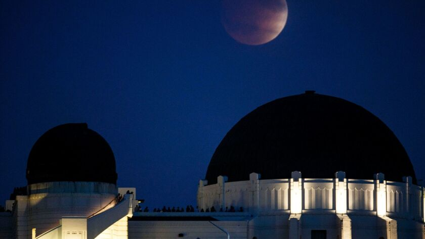 The blood moon rises during a lunar eclipse over the Griffith Observatory on Sunday, September 27, 2