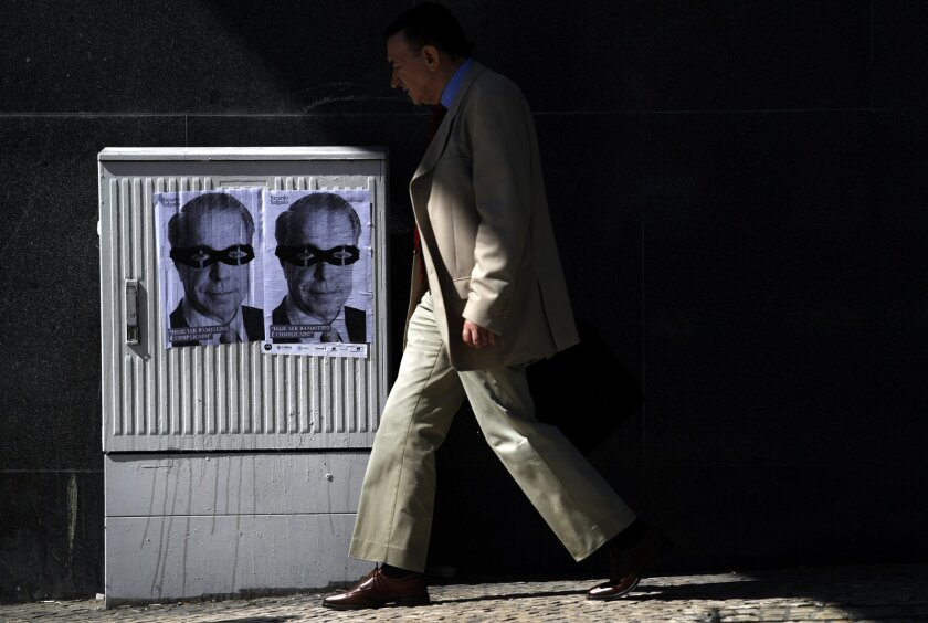 """A man walks past posters with the face of Portuguese bank Banco Espirito Santo's former chief executive Ricardo Salgado depicting him wearing a mask and reading in Portuguese: """"It's hard to be a banker nowadays"""", in Lisbon, Monday, Aug. 4, 2014. Portugal's biggest banking scandal, which compelled authorities Sunday to put up euro 4.9 billion ($6.6 billion) to prevent the collapse of ailing Banco Espirito Santo, raised key questions about how regulators were apparently hoodwinked and focused minds on the European banking system stress tests, whose results are due in October. (AP Photo/Francisco Seco)"""