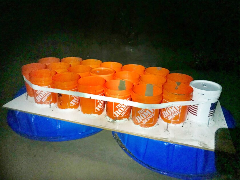 Buckets are taped together and sit on a plywood board on top of two kiddie pools.