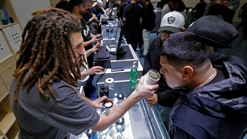 Shant Damirdjian, left, assists customers at the grand opening of Cookies Los Angeles, which sells recreational marijuana under Proposition 64.