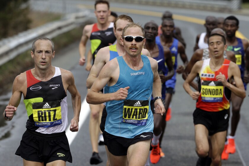 FILE - In this April 15, 2019, file photo, Jared Ward, center, of Mapleton, Utah, leads the pack during the 123rd running of the Boston Marathon in Natick, Mass. Elite runners competing in teams of three from places like Zimbabwe, Peru, Ecuador and across the U.S. will take the starting line Saturday, Sept. 12, 2020, for a unique sort of marathon relay race. Ward will be among the participants as he and his teammates race on their home course in Utah.(AP Photo/Steven Senne, File)