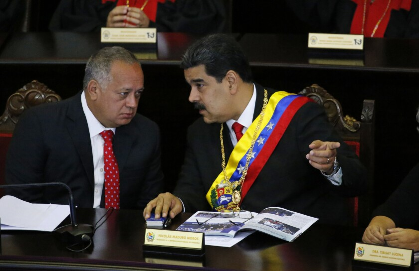 FILE - In this Jan. 24, 2019 file photo, Venezuelan President Nicolas Maduro, right, speaks with Constitutional Assembly President Diosdado Cabello at the Supreme Court during an annual ceremony that marks the start of the judicial year in Caracas, Venezuela. On Thursday, March 26, 2020, the U.S. Justice Department made public it has charged in several indictments against Maduro and his inner circle, including Cabello, that the leader has effectively converted Venezuela into a criminal enterprise at the service of drug traffickers and terrorist groups as he and his allies stole billions from the South American country. (AP Photo/Ariana Cubillos, File)