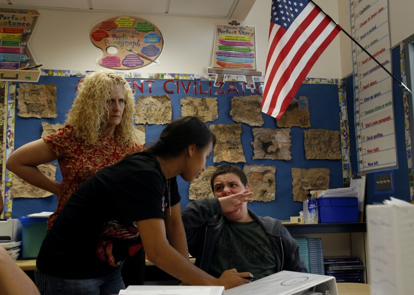 Behavior specialist Michelle May tries to calm down 13-year-old Jonah Funk after he starts biting his hand while working with Sarabeth Rothfeld, in back, at Hesby Oaks School in Encino.