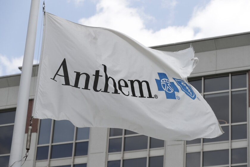 FILE - In this May 14, 2019, file photo a flag flies the outside of the corporate headquarters building of health insurance company Anthem is shown in Indianapolis. Anthem and Wall Street are starting 2021 with different ideas for how the health insurer's year will turn out. The Blue Cross-Blue Shield insurer said Wednesday that it expects adjusted annual earnings to be greater than $24.50 per share, counting hits it expects from the COVID-19 pandemic and a recently passed Congressional spending bill. (AP Photo/Michael Conroy, File)