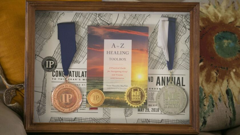 """A shadow box showcases Susan Hannifin-MacNab's book """"A to Z Healing Toolbox"""" and two of the three awards it has won."""