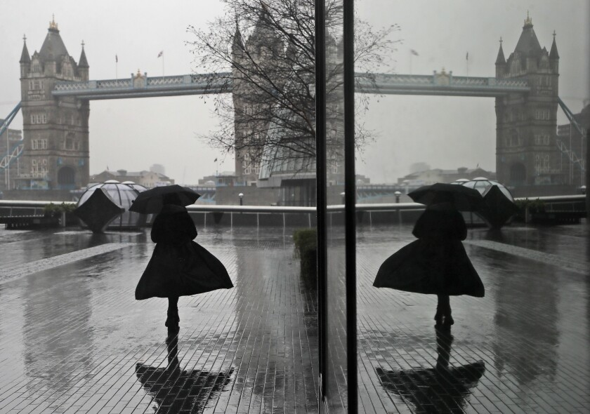 A woman is reflected in a window as she braves wind and rain while walking towards Tower Bridge in London, Thursday, Jan. 14, 2021 during England's third national lockdown to curb the spread of coronavirus. (AP Photo/Kirsty Wigglesworth)