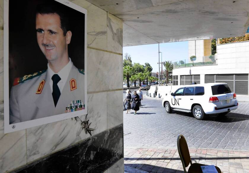 A U.N. vehicle carrying inspectors from the Organization for the Prohibition of Chemical Weapons leaves a hotel in Damascus, where Syrian President Bashar Assad's image adorns a wall.