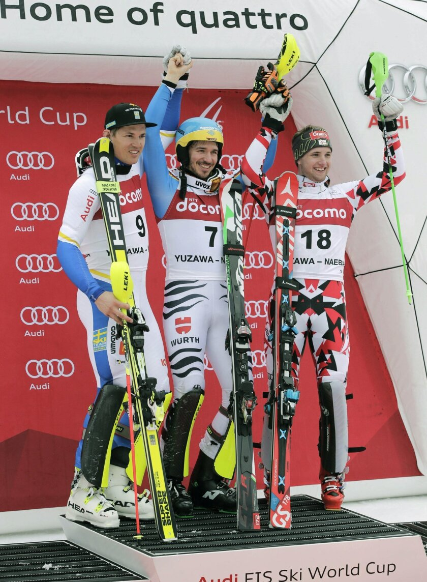 Men's World Cup slalom winner Felix Neureuther, center, of Germany smiles with second placer, Andre Myhrer, left, of Sweden and third placer Marco Schwarz of Austria during the awarding ceremony at the FIS Alpine Ski World Cup Sunday, Feb. 14, 2016, in Yuzawa, northern Japan. Neureuther, fifth afte