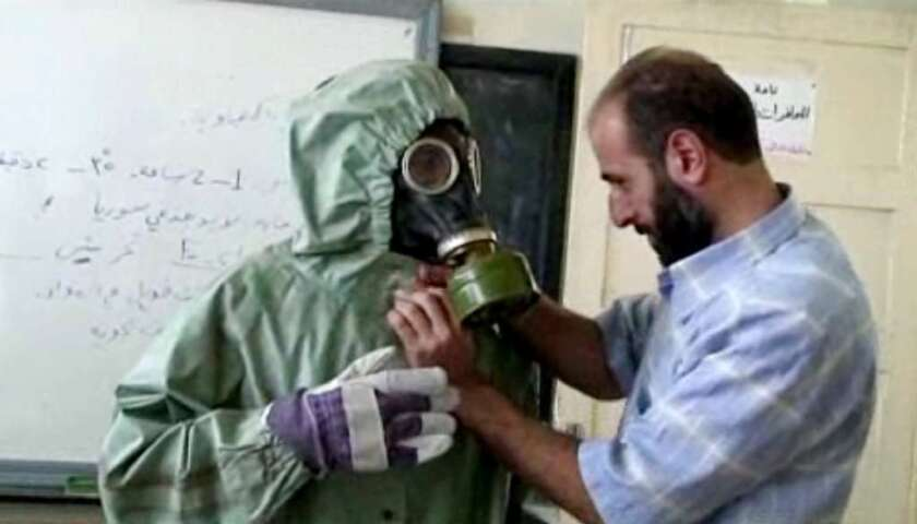 This image made from an AP video posted on Wednesday, Sept. 18, 2013 shows a volunteer adjusting a students gas mask and protective suit.
