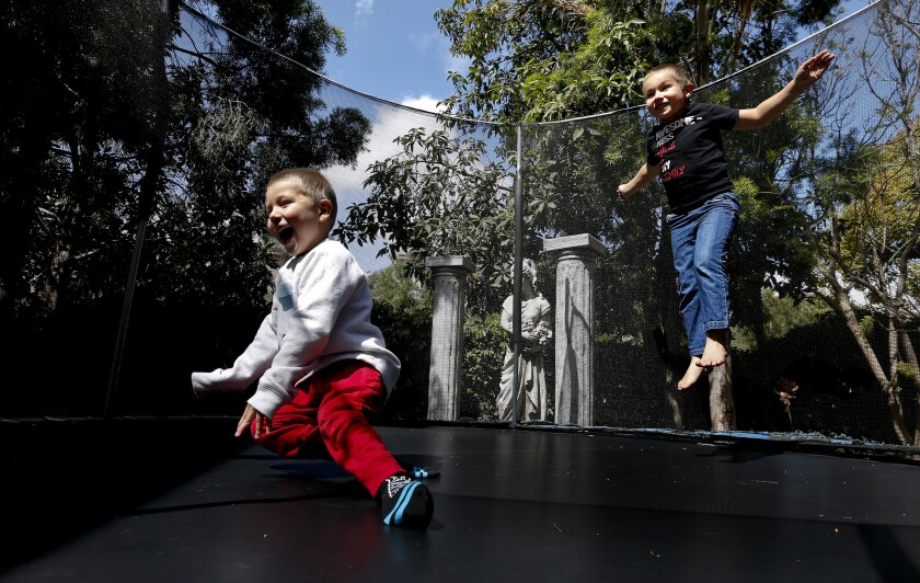 Lucian Olivera, left, and his brother Nikolas play on a trampoline at their home in Moorpark.