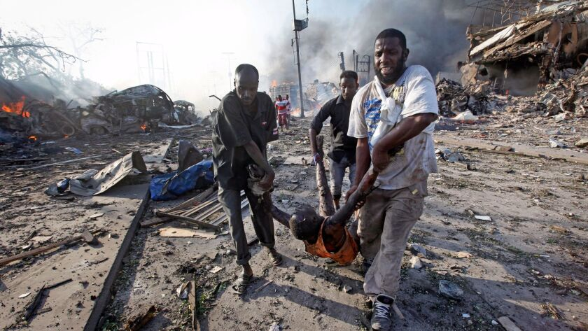Somalis remove the body of a man killed in a blast in the capital Mogadishu, Somalia Saturday, Oct.