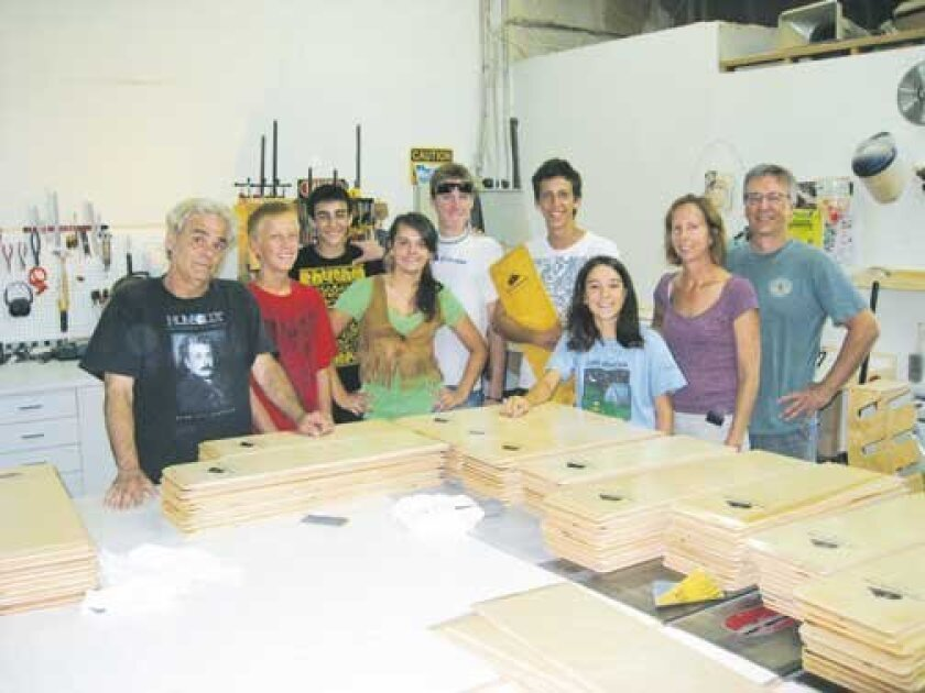 Posing with the side transfer boards are, from left: Markus Unterberg, owner of San Diego Woodworking; Ian St. Louis; Andres Sheikh; Kendall Condon; Austin Farmer; Zac St. Louis; Alice-Anne Carriere; and Anne and Dan St. Louis