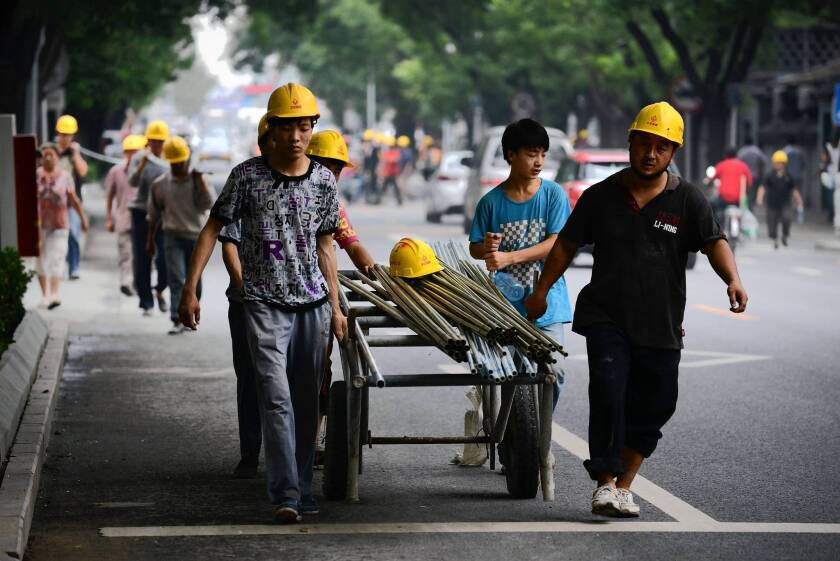 Workers move steel tubes near a construction site in Beijing. In China, reining in credit will squeeze banks and borrowers, including real estate developers.