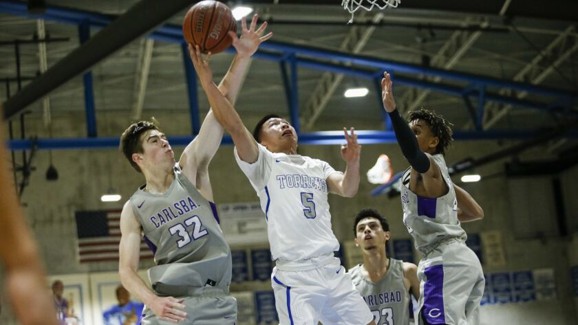 La Jolla Country Day point guard Ray Lu (5) hits a layup under coverage from Carlsbad's Caleb Nelson (32) and Jailen Nelson (10), right, in the first quarter.