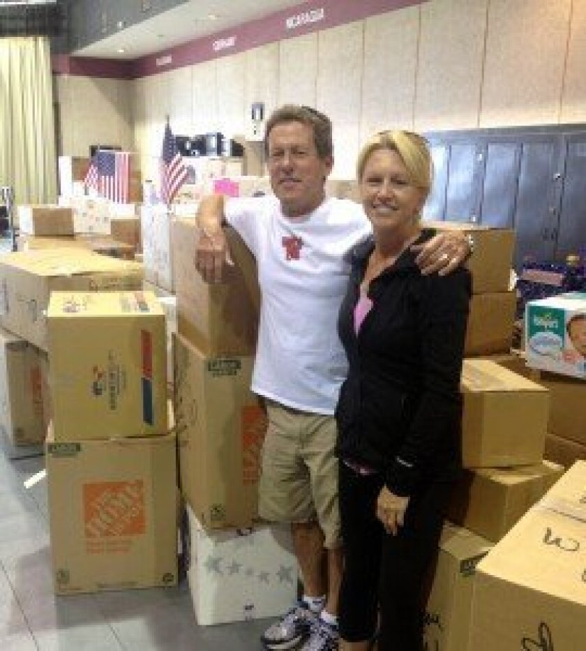 La Jolla Beach Barber Tract residents Gordon and Maureen Dunfee stand beside more than 300 boxes of food, clothing and other supplies they drove to Oklahoma to aid the tornado victims. Courtesy