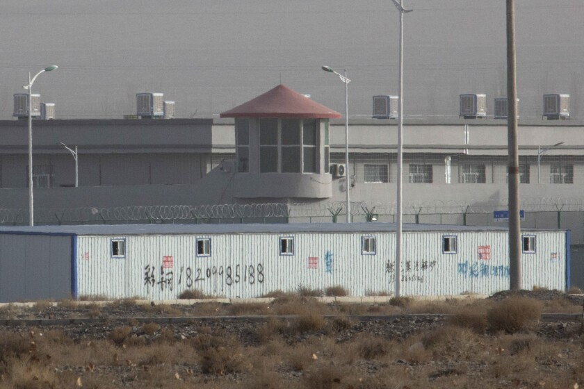 A guard tower and fences are seen around a facility in China's Xinjiang region.