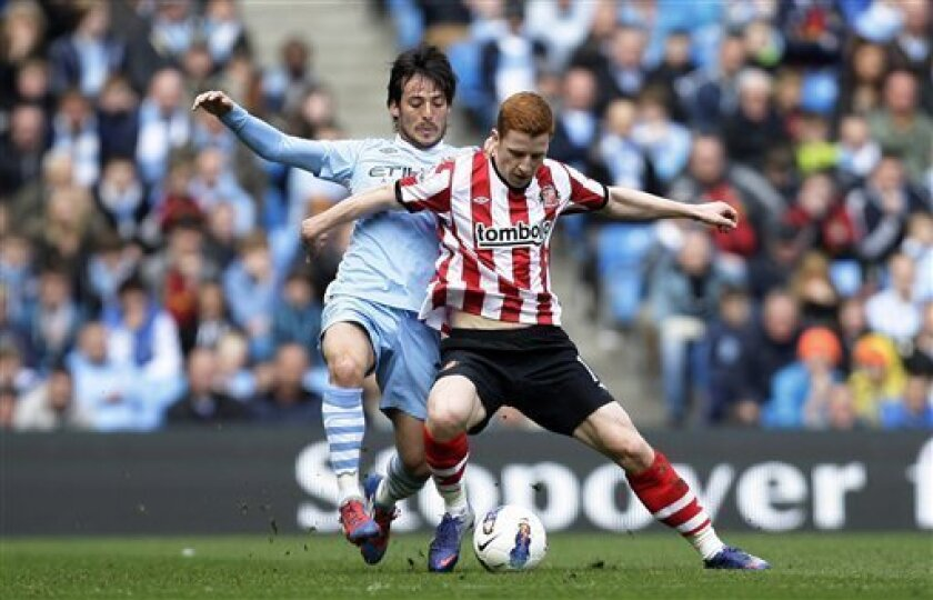Manchester City's David Silva, left, fights for the ball against Sunderland's Jack Colback during their English Premier League soccer match at The Etihad Stadium, Manchester, England, Saturday, March 31, 2012. (AP Photo/Jon Super)