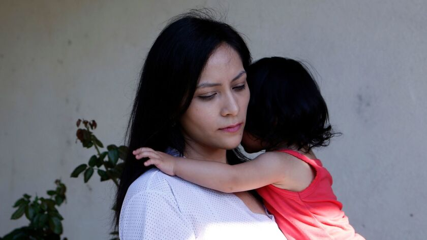 Venecia Yanez holds her 1-year-old daughter Mia outside their home in Paramount. Air quality regulators have detected a potent cancer-causing metal in the city at 350 times normal levels.