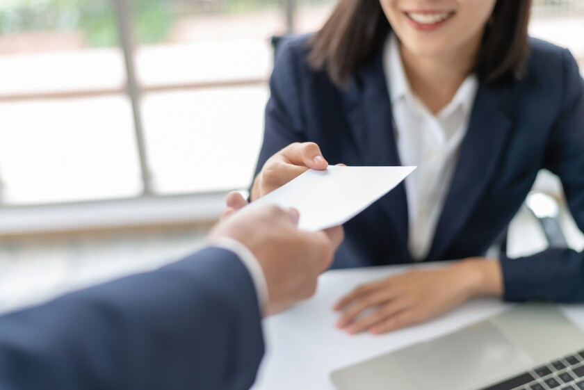 businesswoman handing check to businessman