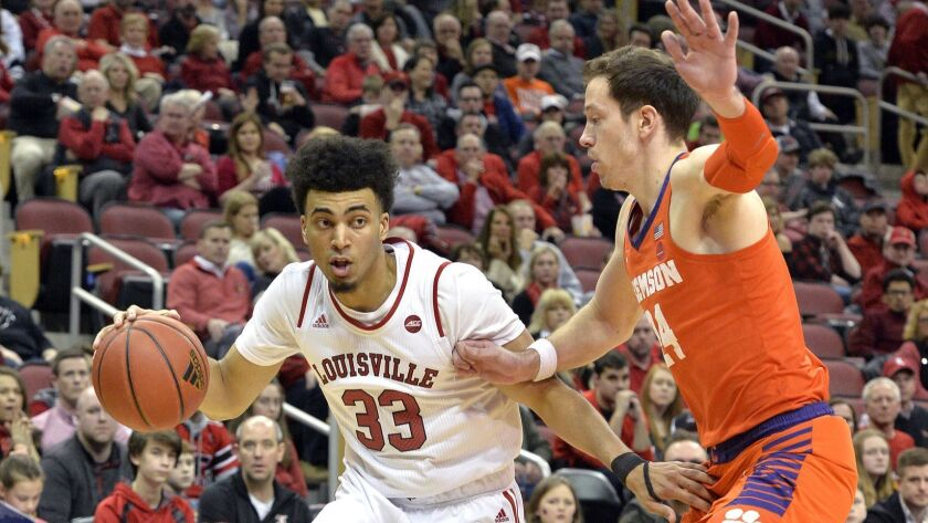 Louisville forward Jordan Nwora (33) attempts to drive past the defense of Clemson forward Elijah Th