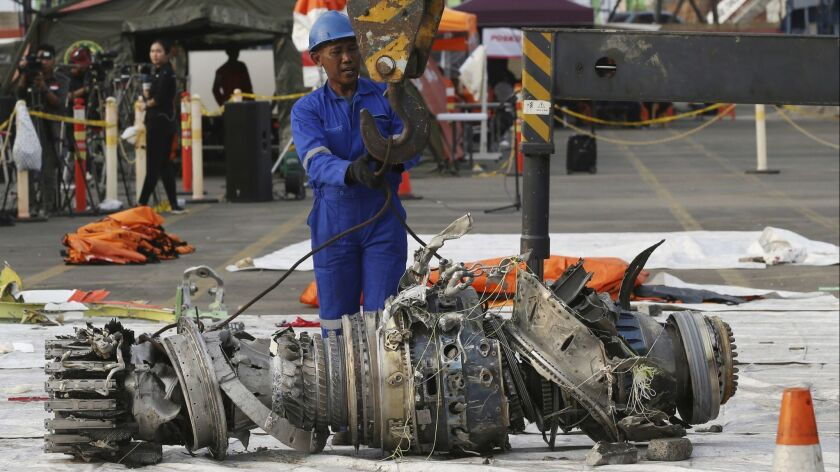 FILE - In this Nov. 4, 2018 file photo, officials move an engine recovered from the crashed Lion Air