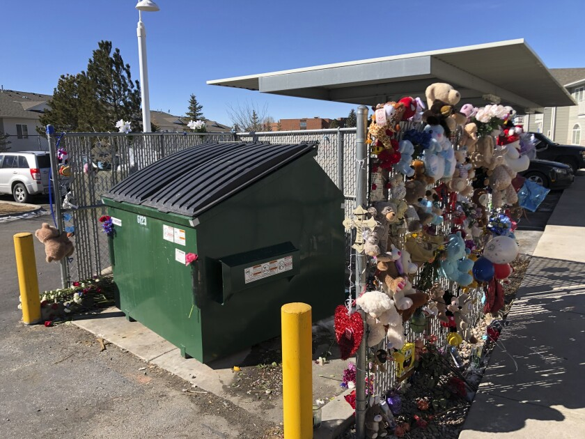 Stuffed animals and notes of condolences are seen attached to a fence Monday, Feb. 22, 2021, around a dumpster at a Cheyenne, Wyo., apartment complex where a 2-year-old boy was found dead. The toddler's body was found in a dumpster several hours after he was reported missing Friday, Feb. 19. (AP Photo/Mead Gruver)