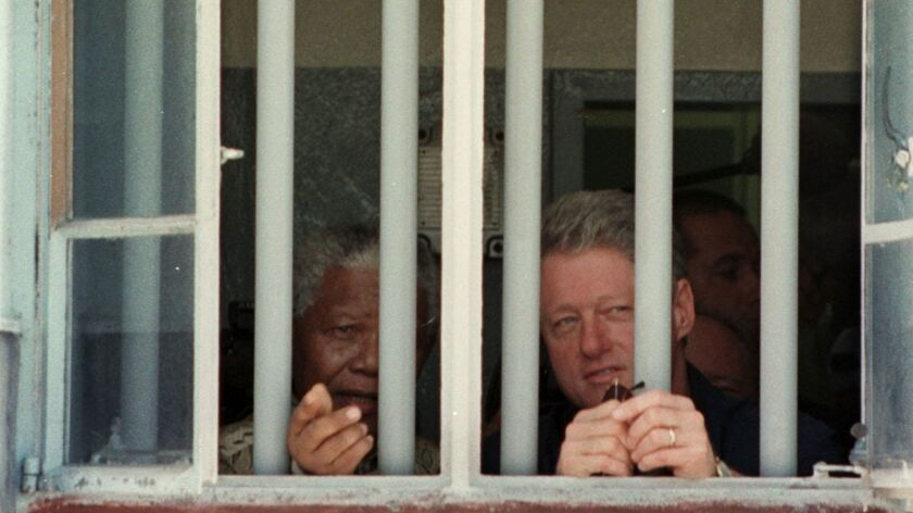 South African President Nelson Mandela and then-U.S. President Bill Clinton peer out of the window of the jail cell at Robben Island, where Mandela spent 18 of the 27 years he was in prison.