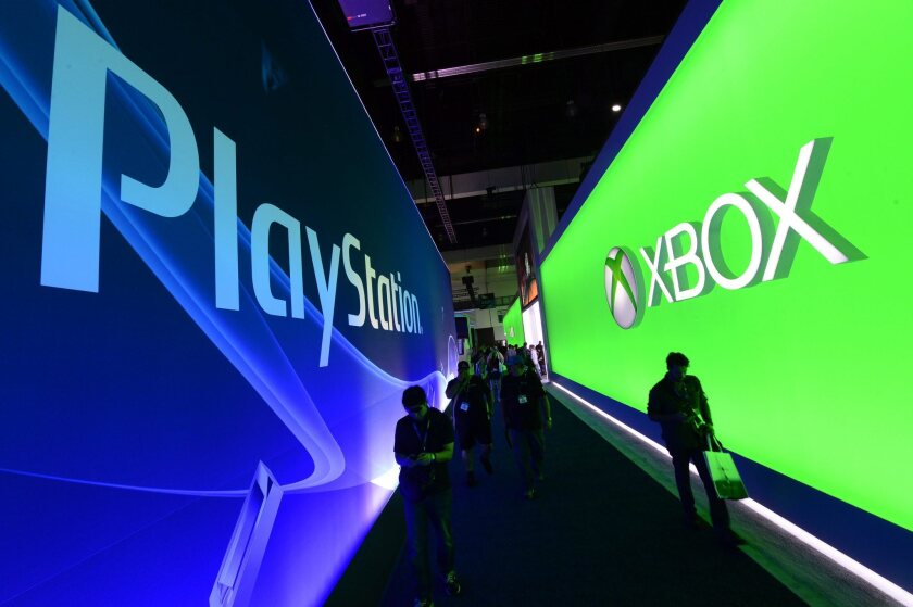Visitors walk between the Xbox and PlayStation exhibition booths on the opening day of E3 on Tuesday.